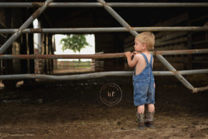 lapeer boy at dairy farm standing by a gate wearing boots and denim overalls for milestone photography