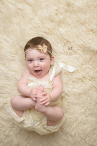 six month old girl from north branch smiles at camera for milestone session with kat fantin with white fur rug and matching romper and headband