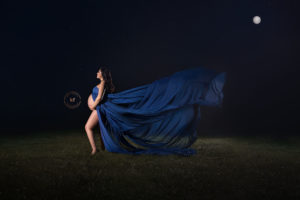 pregnant mother in blue dress posing for lapeer maternity photography session