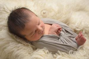 sleeping newborn in lapeer studio with grey wrap and ivory flokati rug