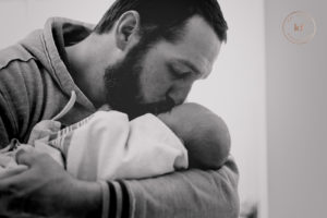 lapeer dad kissing newborn baby for hospital picture by kat fantin photography