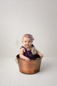 one year old girl in copper bucket on white background in lapeer photography studio for milestone photos