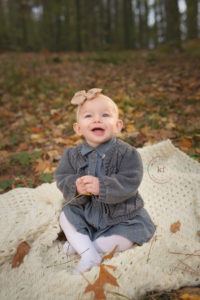 baby girl at lapeer tree farm smiling in leaves
