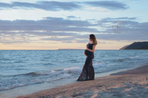 maternity photo of lapeer woman in blue gown on a beach at sunset