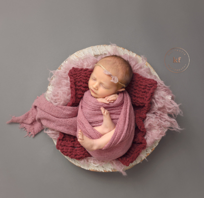 sleeping_newborn_girl_in_bowl_with_pink_wrap_studio_lapeer