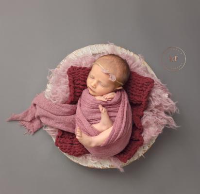 sleeping_newborn_girl_in_bowl_with_pink_wrap_studio_lapeer